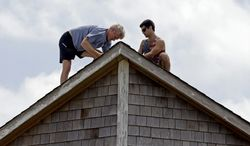 Bruce Liffiton, left, and Brad Fletcher make roof repairs to a vacation cottage on the beach in Nags Head, N.C. after Hurricane Arthur moved through the Outer Banks, Friday, July 4, 2014. Proving far less damaging than feared, Hurricane Arthur left tens of thousands of people without power Friday in a swipe at North Carolina's dangerously exposed Outer Banks, but the weather along the narrow barrier islands had already cleared by Friday afternoon. (AP Photo/Gerry Broome)