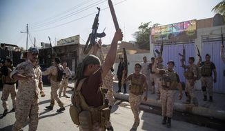 Iraqi security forces celebrate after clashes with followers of Shiite cleric Mahmoud al-Sarkhi, in front of his home in the Shiite holy city of Karbala, 50 miles (80 kilometers) south of Baghdad, Iraq, Wednesday, July 2, 2014. (AP Photo/Ahmed al-Husseini)