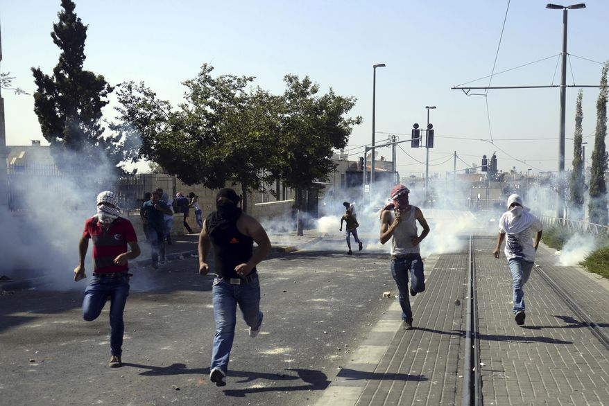 Palestinians run away from tear gas as they clash with Israeli security forces during the funeral of 16-year-old Mohammed Abu Khdeir in Jerusalem on Friday, July 4, 2014. Israeli police clashed with Palestinian protesters in Jerusalem on Friday as thousands of people converged on a cemetery for the burial of an Arab teenager, who Palestinians say was killed by Israeli extremists in a suspected revenge attack. (AP Photo/Mahmoud Illean)