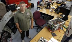 ADVANCED FOR RELEASE SUNDAY, JULY 6, 2014 Jeremy Daily, founder of Synercon Technologies LLC in Tulsa, poses for a photo while working on black-box technology that reveals forensic data in large vehicle crashes in Tulsa, Okla. (AP Photo/Journal Record, Rip Stell)