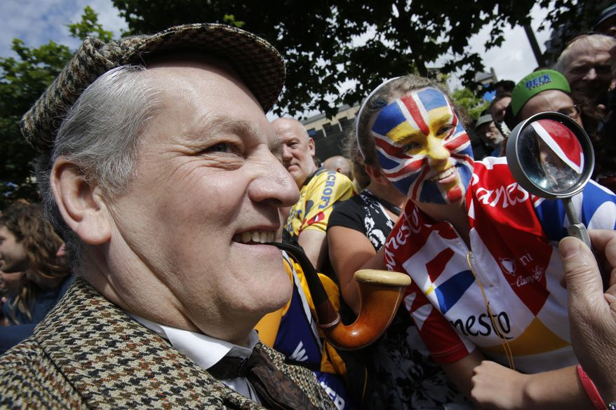 A man dressed as Sherlock Holmes, the fictional detective created by Scottish author and physician Sir Arthur Conan Doyle, left, poses with cycling fans prior to the start of the first stage of the Tour de France cycling race over 190.5 kilometers (118.4 miles) with start in Leeds and finish in Harrogate, Britain, Saturday, July 5, 2014. (AP Photo/Christophe Ena)