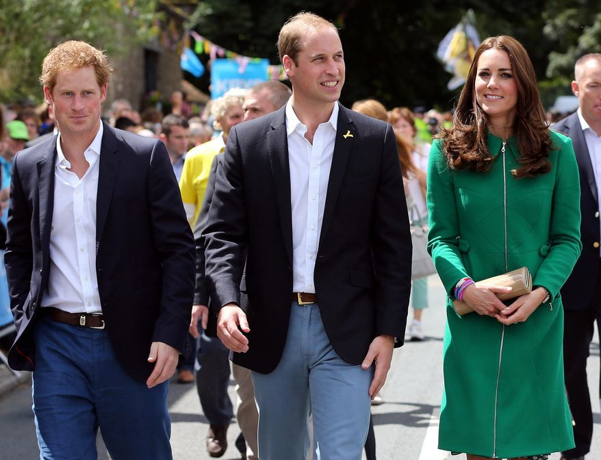 Prince William, centre, Kate Duchess of Cambridge and Prince Harry walk along the street to celebrate the start of the Tour de France in Yorkshire at West Tanfield, England, Saturday, July 5, 2014. The 198 competitors in the 101st Tour de France have started their grueling three-week ride through four countries before ending the world's greatest cycling race in Paris on July 27. (AP Photo/Scott Heppell/Pool)