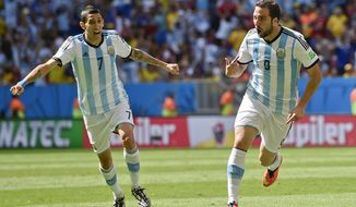 Argentina's Gonzalo Higuain, right, celebrates with Angel di Maria after scoring the opening goal during the World Cup quarterfinal soccer match between Argentina and Belgium at the Estadio Nacional in Brasilia, Brazil, Saturday, July 5, 2014. (AP Photo/Martin Meissner)