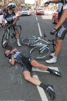 Teammates call for medical assistance after Britain's sprinter Mark Cavendish crashed in the last kilometers of the first stage of the Tour de France cycling race over 190.5 kilometers (118.4 miles) with start in Leeds and finish in Harrogate, England, Saturday, July 5, 2014. (AP Photo/Fred Mons, Pool)
