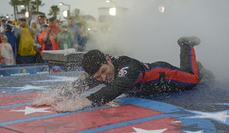 Ryan Truex dives on the rain slick runway during introductions before the NASCAR Sprint cup Series auto race at Daytona International Speedway in Daytona Beach, Fla., Saturday, July 5, 2014. The race was later postponed till Sunday at 11am.(AP Photo/Phelan M. Ebenhack)