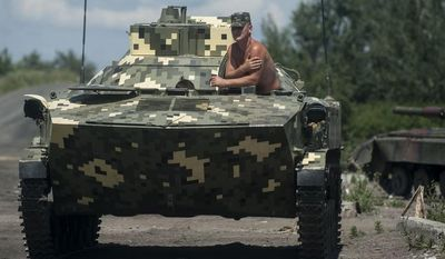 A Ukrainian paratrooper sits in an APC at a checkpoint near Slovyansk, eastern Ukraine, Saturday, July 5, 2014. Ukraine's forces claimed a significant success against pro-Russian insurgents on Saturday, chasing them from one of their strongholds in the embattled east of the country. Rebels fleeing from the city of Slovyansk vowed to regroup elsewhere and fight on.  (AP Photo/Evgeniy Maloletka)