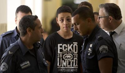 """Tariq Abu Khdeir, 15, a U.S. citizen who relatives say was beaten and arrested by Israeli police during clashes sparked by the killing Thursday of his cousin Mohammed Abu Khdeir, is escorted by Israeli prison guards during an appearance at Jerusalem magistrate's court Sunday, July 6, 2014. Israeli  police said Tariq Abu Khdeir resisted arrest, attacked officers and was carrying a slingshot for lobbing stones when he was arrested. He has been sentenced to nine days of house arrest. The U.S. State Department said it was """"profoundly troubled"""" by reports of his beating and demanded an investigation. (AP Photo/Oded Balilty)"""