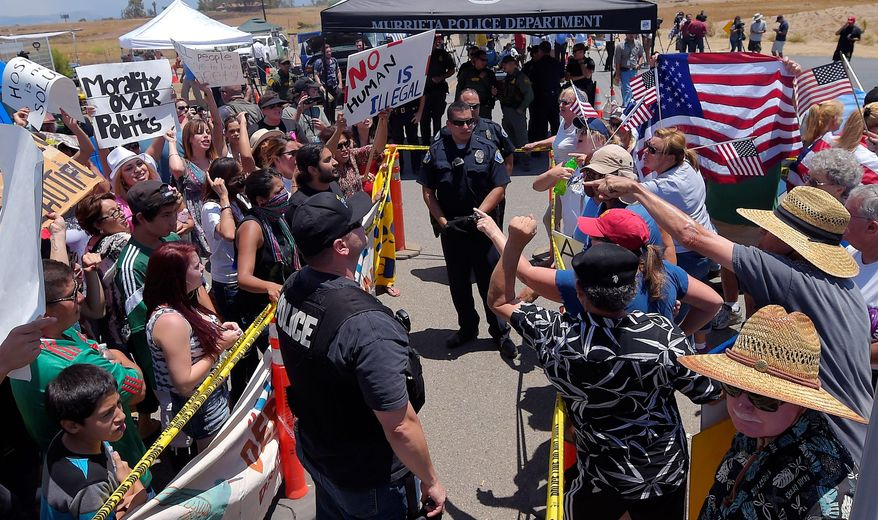 Demonstrators on opposing sides of the immigration debate are separated by police officers Friday outside a U.S. Border Patrol station in Murrieta, California. The town was the latest flashpoint for standoffs over the transport of illegal minor immigrants. (Associated Press)