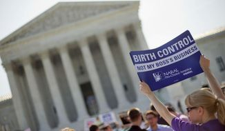 ** FILE ** This June 30, 2014, file photo shows a demonstrator holding up a sign outside the Supreme Court in Washington on the day the court decided in the Hobby Lobby case to relieve businesses with religious objections of their obligation to pay for women's contraceptives among a range of preventive services the new health law calls for in their health plans. (AP Photo/Pablo Martinez Monsivais, File) **FILE**