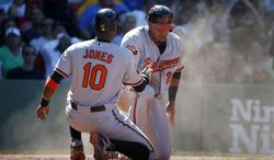 Baltimore Orioles' Adam Jones, left, and Nelson Cruz, right,  celebrate after scoring on an RBI single by J.J. Hardy in the seventh inning of a baseball game against the Boston Red Sox in Boston, Sunday, July 6, 2014. (AP Photo/Michael Dwyer)