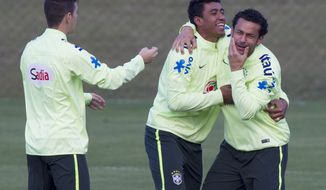 Brazil's soccer players, Fred, right, Paulinho, center and Oscar, joke around during a practice session at the Granja Comary training center, in Teresopolis, Brazil, Sunday, July 6, 2014. Brazil will face Germany on Tuesday in their World Cup semifinals' match, without superstar soccer player Neymar. (AP Photo/Leo Correa)