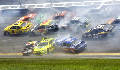Kasey Kahne, front left, Paul Menard (27) and Reed Sorenson (36) are among the cars that crashed coming out of the backstretch going in to turn 3 during the NASCAR Sprint cup Series auto race at Daytona International Speedway in Daytona Beach, Fla., Sunday, July 6, 2014. (AP Photo/Ron Sanders)