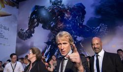 """FILE - In this June 23, 2014 file photo, director Michael Bay, center, gestures to fans as he attends the premiere of movie """"Transformers: Age of Extinction"""" at a theatre in Beijing, China. The latest """"Transformers"""" movie, which features Chinese locations, actors and products, has so far earned almost as much in China as in the United States, driven by a record number of screenings for a foreign movie. """"Transformers: Age of Extinction"""" has made an estimated $149 million in the U.S. and $134 million in China, the world's biggest and second-biggest movie markets, respectively, according to figures from box office tracking website Box Office Mojo. (AP Photo/Alexander F. Yuan, File)"""