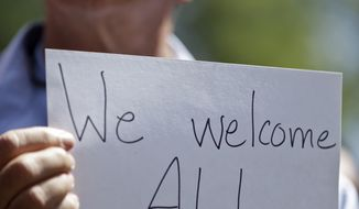 A man holds up a sign during a rally in support of immigrants in San Diego. A Texas bishop said Sunday that the debate over unaccompanied youths at the southern U.S. border has focused on their illegal status and what to do with them but has ignored the root causes of the problem.  (AP Photo/Gregory Bull)