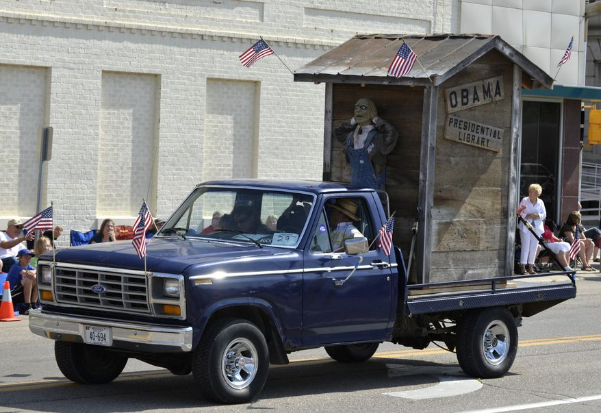 """A float with the words """"Obama Presidential Library"""" is seen during the Fourth of July parade in downtown Norfolk, Neb., Friday morning, July 4, 2014. The float has received criticism from  a city councilman and the Nebraska Democratic Party, and others. (AP PHOTO/NORFOLK DAILY NEWS/Darin Epperly)"""