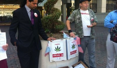 Activists Nikolas Schiller (left) and Adam Eidinger (right) outside the D.C. Board of Elections display some 57,000 petition signatures collected in support of a referendum to legalize marijuana (Andrea Noble/The Washington Times)