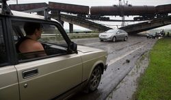 Cars ease under a destroyed railroad bridge near the village of Novobakhmutivka, located north of Donetsk in eastern Ukraine. Bridges leading into Donetsk were likely destroyed to slow government forces from moving on the rebel-held stronghold. (associated press)