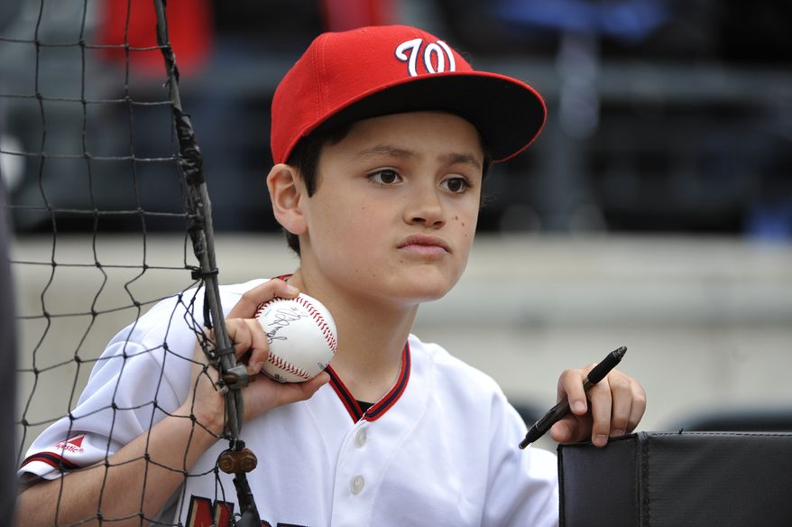 Washington Nationals fan Derick  Benzinger, 9, of Cedar Grove, New Jersey looks for autographs during batting practice before the baseball gamebetween the New York Mets and the Nationals at Citi Field on Friday, April 19, 2013 in Flushing, N.Y. (AP Photo/Kathy Kmonicek)
