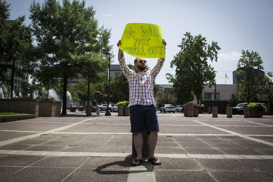 """Trevor Berryhill, 29, stands with his, """"We will not chill out,"""" sign while protesting outside of City Hall while City Council members discuss retirement plan options inside the facility in Memphis, Tenn., on July 1, 2014. Berryhill said his father is a sergeant with the Memphis Police Department. (Associated Press/The Commercial Appeal)"""