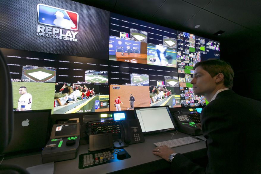 Chris Marinak sits in front of a bank of television screens during a preview of Major League Baseball's Replay Operations Center, in New York, Wednesday, March 26, 2014.  (AP Photo/Richard Drew)