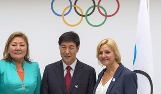Representatives of the 2022 Olympic Games candidate cities, from left to right, Amanzholova Zauresh, vice-mayor of Almaty City representing Almaty 2022, Yang Xiaochao, vice-chairman of Beijing 2022, and Eli Grimsby, CEO of the candidate city of Oslo 2022, pose for photographers during during the announcement of the 2022 Olympic Winter Games candidate cities (Beijing 2022, Oslo 2022, Almaty 2022) after an executive board meeting, at the IOC headquarters in Lausanne, Switzerland, on Monday, July 7, 2014. (AP Photo/Keystone,Jean-Christophe Bott)