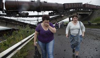 People walk under a destroyed railroad bridge over a main road leading into the east Ukraine city of Donetsk, near the village of Novobakhmutivka,  20 km North from the city of Donetsk, eastern Ukraine Monday, July 7, 2014. The bridge has been destroyed, blocking a key access route to the rebel-held city. (AP Photo/Dmitry Lovetsky)