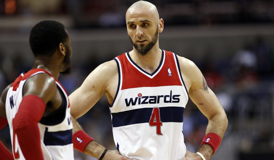 Washington Wizards guard John Wall (2) and center Marcin Gortat (4), from Poland, talk in the first half of an NBA basketball game Wednesday against the Boston Celtics, April 2, 2014 in Washington. (AP Photo/Alex Brandon)