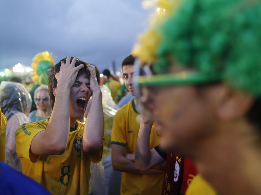 A Brazil soccer fan reacts in frustration as he watches his team play a World Cup semifinal match against Germany on a live telecast inside the FIFA Fan Fest area on Copacabana beach in Rio de Janeiro, Brazil, Tuesday, July 8, 2014. (AP Photo/Leo Correa)