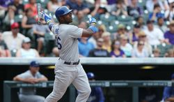 Los Angeles Dodgers' Yasiel Puig follows the flight of his RBI-double against the Colorado Rockies in the eighth inning of a Dodgers' 8-2 victory in a baseball game in Denver, Sunday, July 6, 2014. (AP Photo/David Zalubowski)