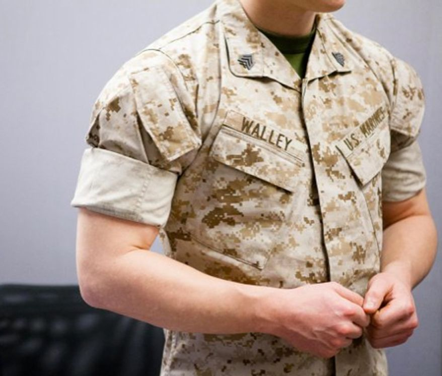 ** FILE ** Pfc. Austin Braun talks to a reporter about rolling sleeves March 10, 2014. When marines transitioned to their desert cammies for warmer weather. (U.S. Army)