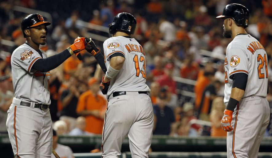 Baltimore Orioles' Manny Machado (13), celebrates his two-run homer with Adam Jones left, with Nick Markakis, at right, during the 11th inning of an interleague baseball game against the Washington Nationals at Nationals Park, Monday, July 7, 2014, in Washington. The Orioles won 8-2, in 11 innings. (AP Photo/Alex Brandon)
