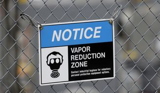 "A sign stating efforts to reduce exposure to vapors is shown at the ""C"" tank farm during a media tour of the Hanford Nuclear Reservation Wednesday, July 9, 2014 near Richland, Wash. Officials said Wednesday that 12,000 air samples taken at Hanford this year after more than three dozen workers reported being sickened by chemical vapors have failed to find a cause for the problem. (AP Photo/Ted S. Warren)"