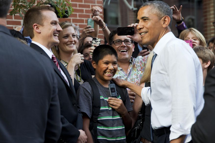 President Barack Obama greets an enthusiastic crowd during an impromptu walk down 15th Street after having dinner at Wazee Supper Club on Tuesday, July 8, 2014, in Denver. (AP Photo/Jacquelyn Martin)