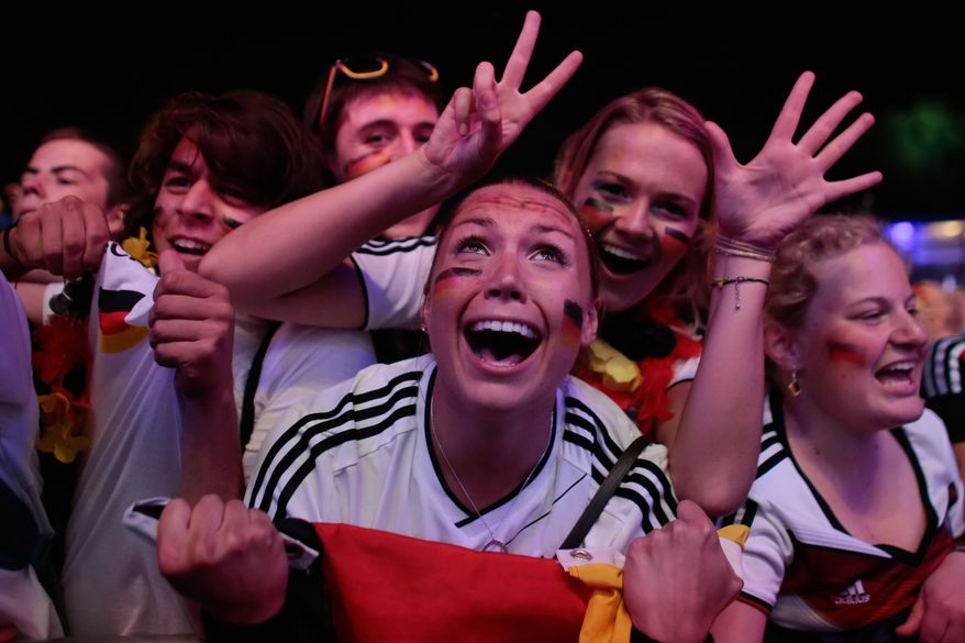 German soccer fans celebrate after their team won the Brazil World Cup semi final being played in Belo Horizonte, Brazil, between Germany and Brazil at a public viewing event called 'Fan Mile' in Berlin, Tuesday, July 8, 2014. (AP Photo/Markus Schreiber)