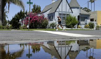 A house is reflected in a puddle of water from an irrigated front yard Wednesday, July 9, 2014, in San Diego. Wasting water outdoors amid the state's drought will begin hitting Californians in the wallet under new restrictions being proposed by state regulators, with fines of up to $500 a day for overwatering front lawns or washing a car without a nozzle on the hose.  (AP Photo/Gregory Bull)
