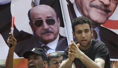 Supporters of Gen. Omar Suleiman chant in front of his posters outside the Higher Presidential Elections Commission in Cairo on Sunday, April 8, 2012. (AP Photo/Amr Nabil)