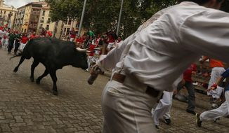 """Revelers run in front of a Victoriano del Rio ranch fighting bull during the running of the bulls of the San Fermin festival, in Pamplona, Spain, Wednesday, July 9, 2014. Revelers from around the world arrive in Pamplona every year to take part on some of the eight days of the running of the bulls glorified by Ernest Hemingway's 1926 novel """"The Sun Also Rises."""" (AP Photo/Daniel Ochoa de Olza)"""