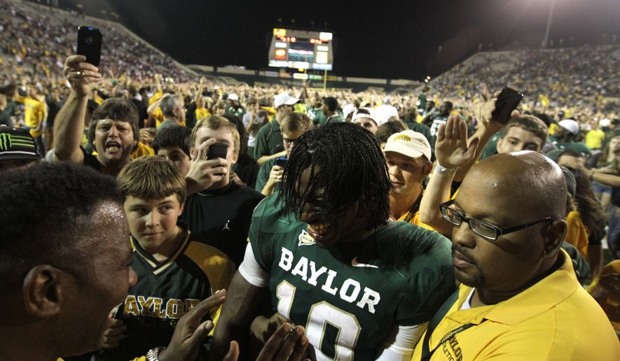 Baylor quarterback Robert Griffin III (10) is surrounded by fans that rushed the field and security as he is escorted off the field following their 45-38 win over Oklahoma in an NCAA college football game Saturday, Nov. 19, 2011, in Waco, Texas. (AP Photo/Tony Gutierrez)