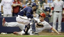 Philadelphia Phillies' Cody Asche slides safely past Milwaukee Brewers catcher Jonathan Lucroy during the fifth inning of a baseball game Tuesday, July 8, 2014, in Milwaukee. Asche scored from second on a hit by Domonic Brown. (AP Photo/Morry Gash)