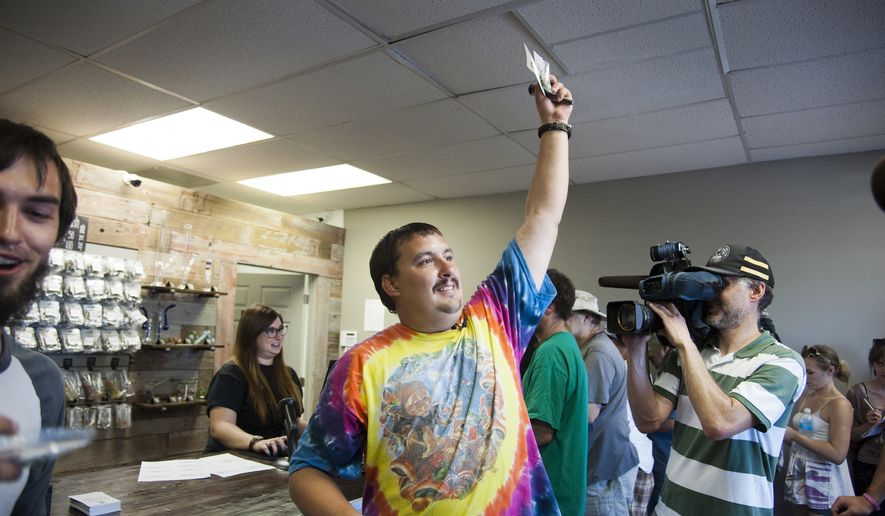 ** FILE ** Mike Boyer turns to the crowd outside, showing off the 4 grams of marijuana he bought as the first in line to legally purchase marijuana at Spokane Green Leaf, Tuesday, July 8, 2014, in Spokane, Wash.  (Associated Press)