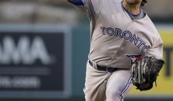 Toronto Blue Jays starting pitcher R.A. Dickey throws to the Los Angeles Angels during the first inning of a baseball game in Anaheim, Calif., Tuesday, July 8, 2014. (AP Photo/Chris Carlson)