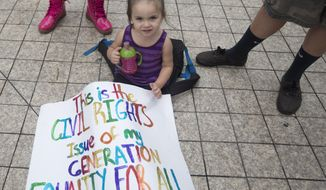 FILE- In this July 2, 2014 photo file, an unidentified child of a same sex couple sits next to a protest sign during the court hearing on gay marriage in Miami. Many religious leaders and conservative groups want President Obama to exempt religious organizations from an executive order barring federal contractors from discriminating against gays in hiring. (AP Photo/J Pat Carter, File)