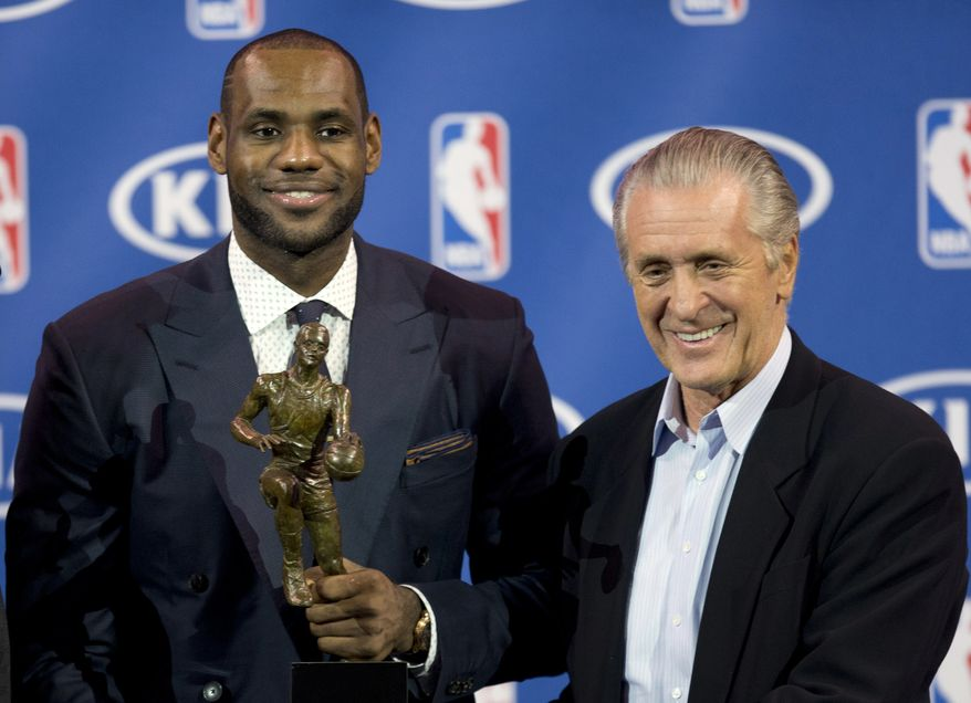 In this May 5, 2013 photo, Miami Heat NBA basketball player LeBron James, left, holds his NBA Most Valuable Player award as he poses with team president Pat Riley, in Miami. Before James makes his next decision, Riley will get a chance to convince him to stay in Miami. Two people familiar with the situation told The Associated Press late Sunday night, July 6, 2014, that James will meet with the Heat president this week before making a decision about where to play next season. (AP Photo/J Pat Carter)