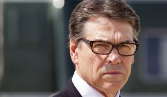 Texas Gov. Rick Perry waits to meet President Barack Obama on arrival in Dallas where they will attend a meeting on immigration, Wednesday, July 9, 2014. (AP Photo/Jacquelyn Martin)