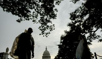 Torsten Peterson of Denmark puts on a plastic rain cover as he makes his way along the National Mall near the U.S. Capitol Building, Washington, D.C., Wednesday, July 9, 2014. (Andrew Harnik/The Washington Times)