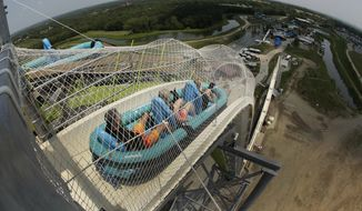 """In this photo taken with the fisheye lens, riders go down the world's tallest water slide called """"Verruckt"""" at Schlitterbahn Waterpark, Wednesday, July 9, 2014, in Kansas City, Kan. (AP Photo/Charlie Riedel) ** FILE **"""