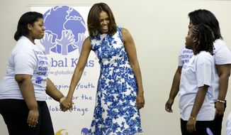 First lady Michelle Obama holds hands with Jania Nelson, left, as she's escorted by Annie Willis and Alaya Shearman, right, during her visit with members of Global Kids, at Baruch College, in New York,  Thursday, July 10, 2014. Global Kids works to develop youth leaders through global education and leadership development programs. (AP Photo/Richard Drew)