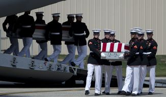 "FILE - This Sept. 14, 2012, file photo shows carry teams at Andrews Air Force Base, Md. moving flag draped transfer cases during the Transfer of Remains Ceremony of the four Americans killed in an attack on a diplomatic outpost and CIA annex Benghazi, Libya. The testimony of nine military officers severely undermines claims by Republican lawmakers that a ""stand-down order"" held back military assets who could have those killed in the attack.  (AP Photo/Carolyn Kaster, File)"
