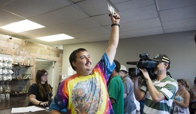 Mike Boyer turns to the crowd outside, showing off the 4 grams of marijuana he bought as the first in line to legally purchase marijuana at Spokane Green Leaf, Tuesday, July 8, 2014, in Spokane, Wash.  (AP Photo/The Spokesman-Review, Dan Pelle)