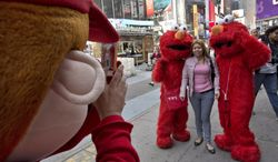 FILE - In this April 9, 2013 file photo, a Super Mario character, left, uses a woman's mobile phone camera to photograph her with a pair of Elmo characters in New York's Times Square.  A New York City Council member is drafting legislation to regulate the costumed characters who roam Times Square. The bill being proposed by Councilman Dan Garodnick would require that the costumed performers be licensed and go through a background check. There have been a number of troublesome incidents involving costumed figures who try to make a living by charming tourists.  (AP Photo/Richard Drew, File)